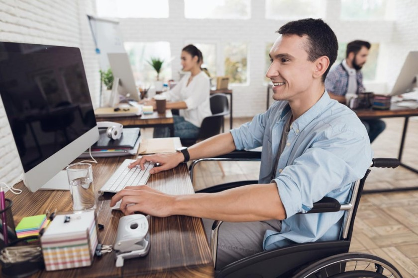 Disabled person in the wheelchair works in the office at the computer.